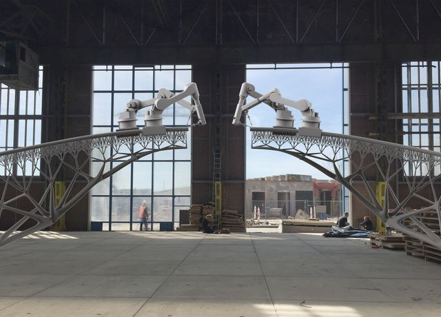 Industrial robot arms building a pedestrian bridge