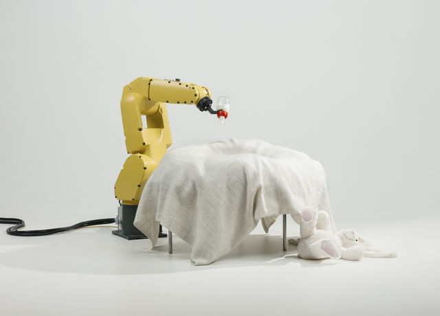 An industrial robot holding a baby's feeding bottle
