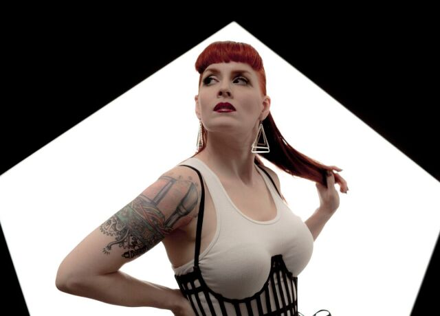 Ana Matronic looking off camera with a white on black pentagon
