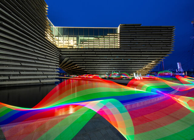 The V&A Dundee building at dusk with rainbow-coloured light trails in the foreground