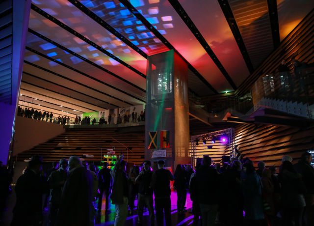 The main body of V&A Dundee filled with people dancing and having fun as the building is dark and lit up with bright, fun colours all over the walls and ceiling.