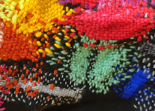Close-up of a jumper that's been darned in many different coloured threads.