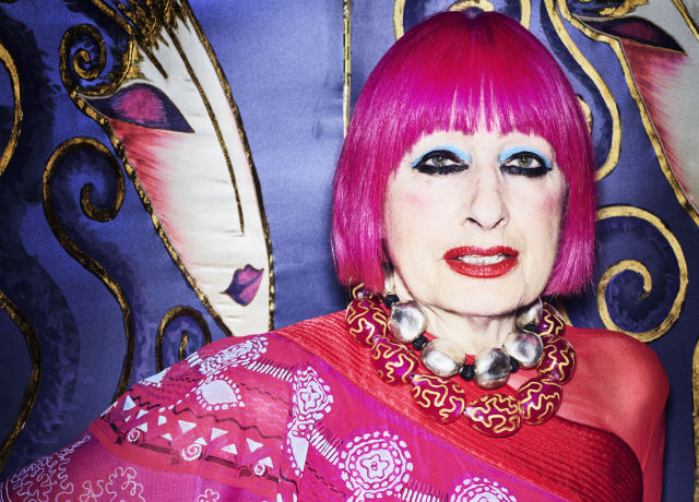 Portrait of Zandra Rhodes with bright pink hair and a pink outfit.