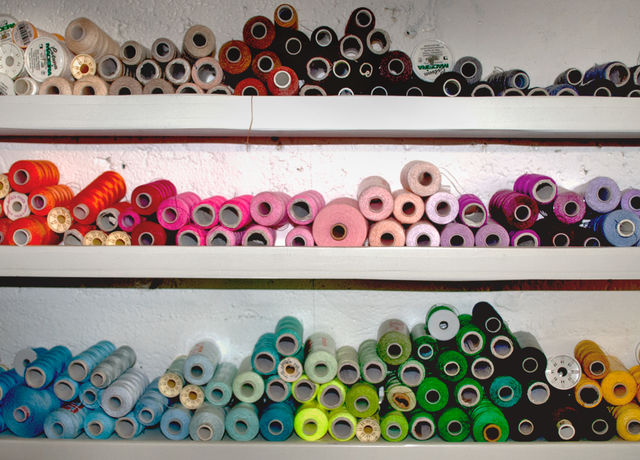 Shelves of sewing thread bobbins in different colours.
