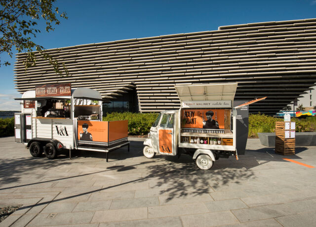 Two vintage style vans outside V&A Dundee in the sunshine.