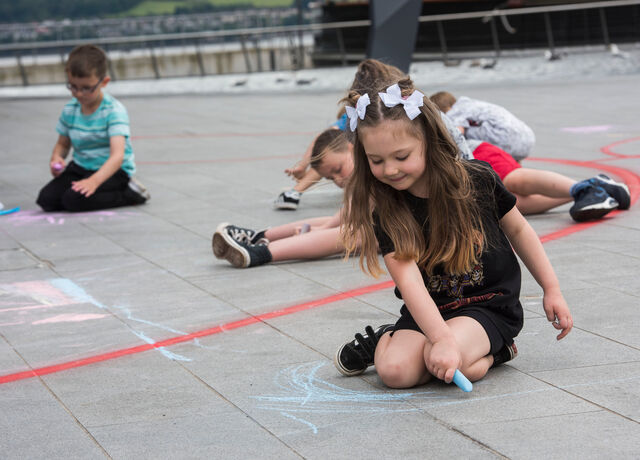 Children playing with chalk on the ground in front of V&A Dundee.