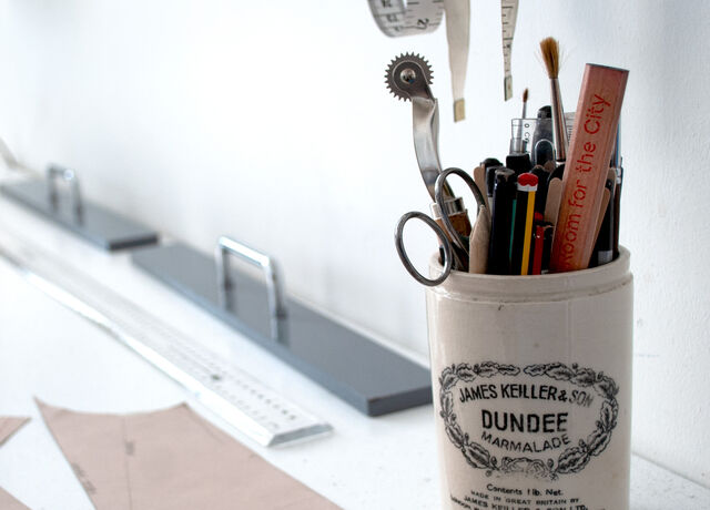 A cream James Keillor & Sons Dundee marmalade pot on a workbench filled with stationery