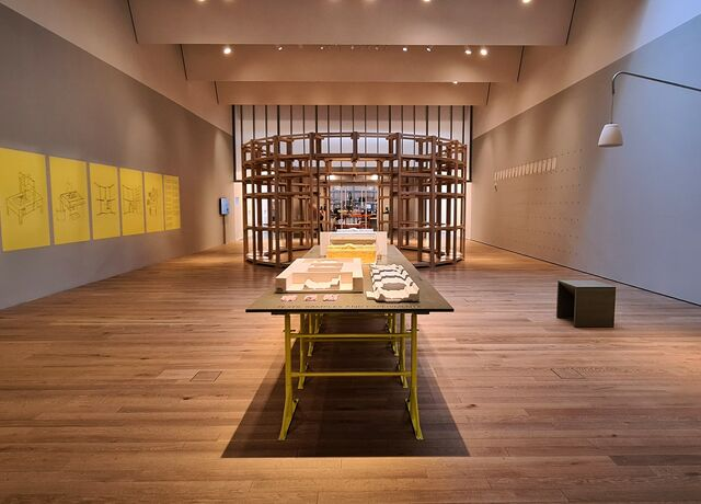 Photo of inside the making room exhibition.  Sketches are hung on the left wall, a table with model samples is in the middle, and a film is playing on the right wall
