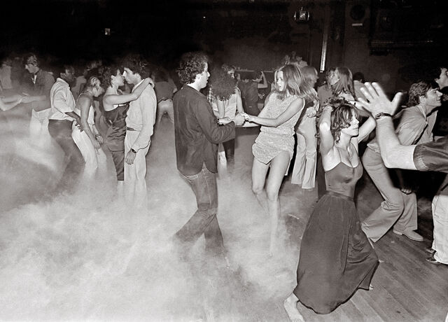 A black and white image of a crowd dancing on a dancefloor