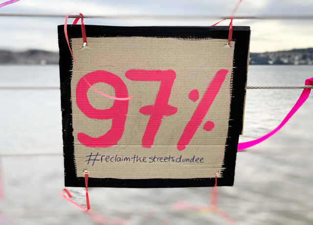 A hand-made cardboard placard with '97%' painted in pink