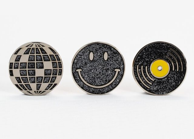 Photo of three enamel pins depicting a disco ball, happy face and record