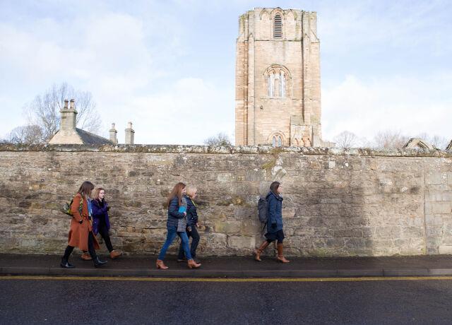 People walking beside a wall in an urban area