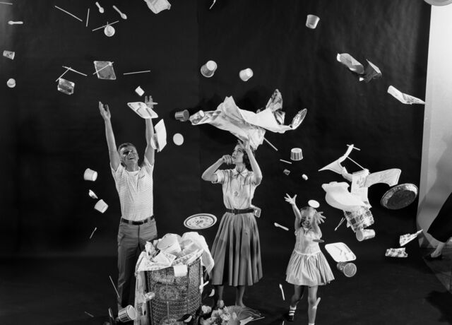 A black and white image of a man, woman and child throwing up plastic into the air