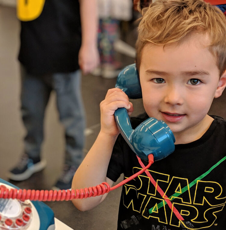 Photo of a boy holding a blue bakelite phone receiver to his head