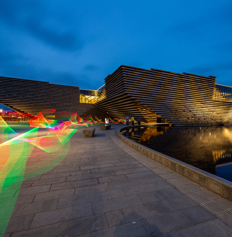 A rainbow ribbon made of light in front of V&A Dundee
