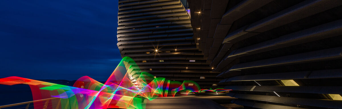 Photo of V&A Dundee at night with a rainbow light trail created using a lightstick on a timelapse