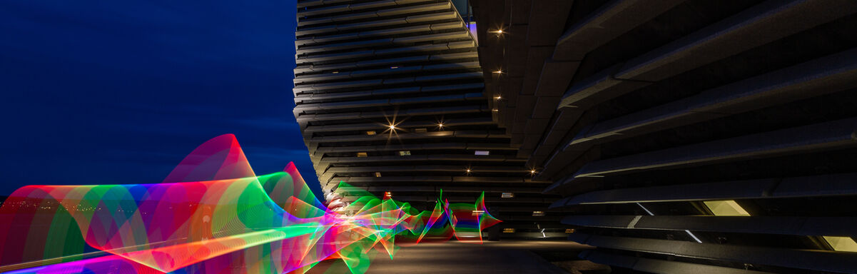 A rainbow coloured light trail along the waterfront behind V&A Dundee