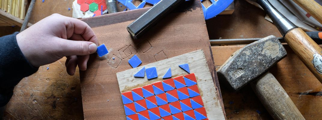 Photo of workbench with red and blue plastic triangles forming a pattern
