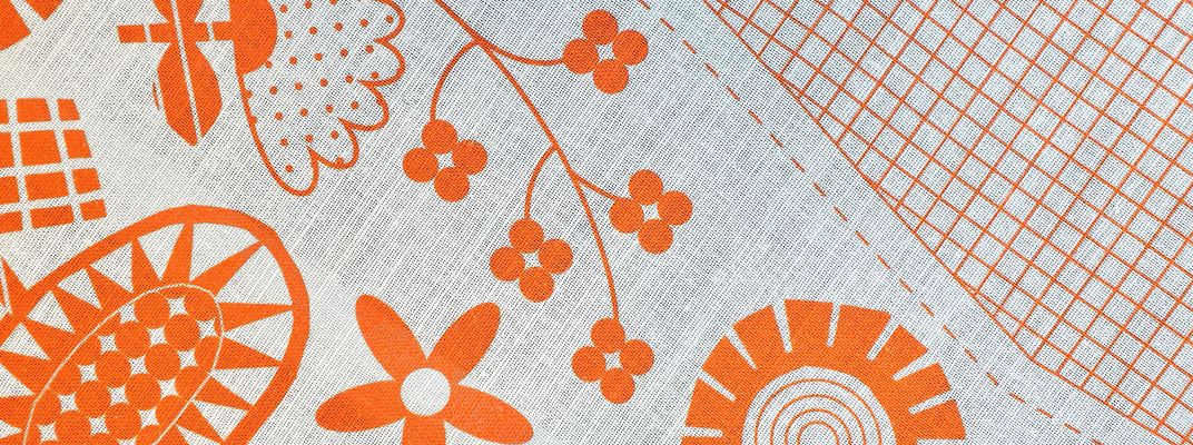 Linen with orange floral shapes on it that can be embroidered onto.